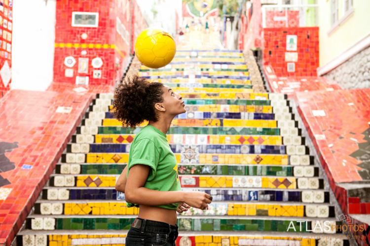 Young woman doing keepy uppys in front of the Escadaria Selaron steps in Rio de Janiero, Brazil