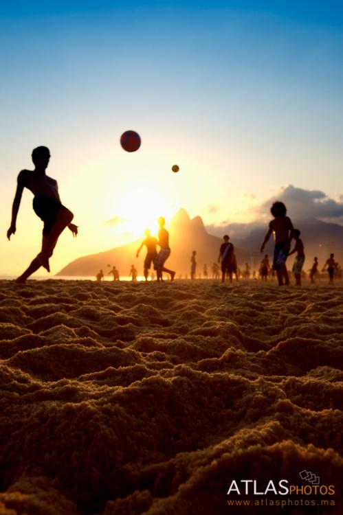 Sunset silhouettes playing altinho futebol beach football kick-ups soccer ball Ipanema Beach Rio de Janeiro Brazil. Image shot 2014. Exact date unknown.