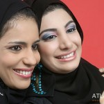 Two Arab Ladies standing cheek to cheek with cell phone