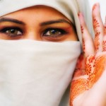 Beautiful woman wears hijab, with hina or hennah painted on palm of hand. Image shot 2006. Exact date unknown.