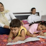 Children reading on the bed while parents watch